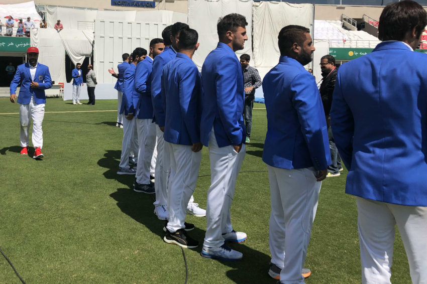 Rashid Khan in shiny blue team blazer, red Test cap, and the matching shoes.